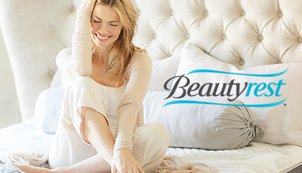 Women laughing alone on bed with Beautyrest logo