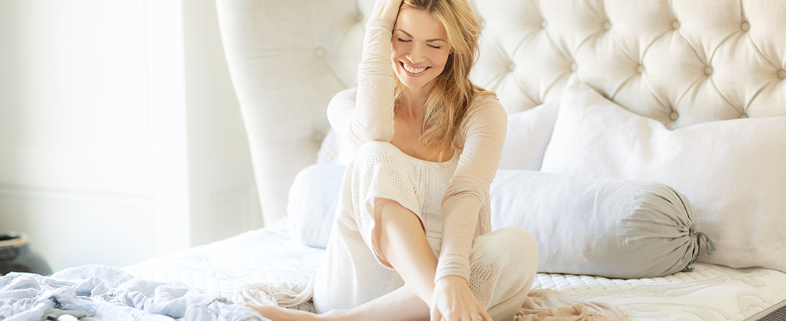 Women laughing alone on bed
