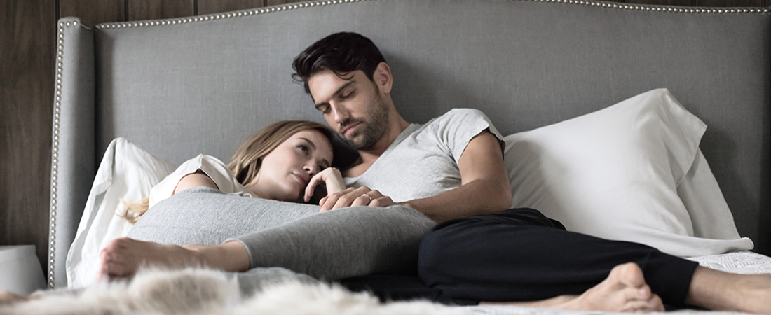 Women gazing longingly on bed with man