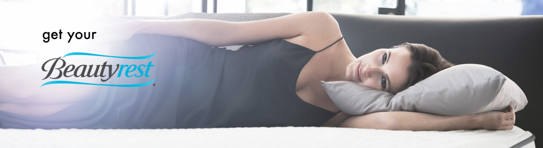 Women sideways on bed with Beautyrest Logo